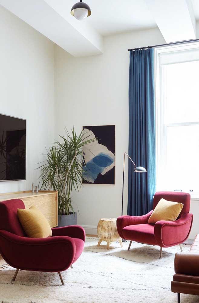 Cortinas azuis para a sala de estar clean e elegante; repare que o contraste com as poltronas vermelhas ficou perfeito