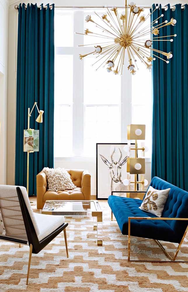 Sala de estar contemporânea e conceitual decorada com tom de azul petróleo e elementos dourados, não podia ficar melhor!