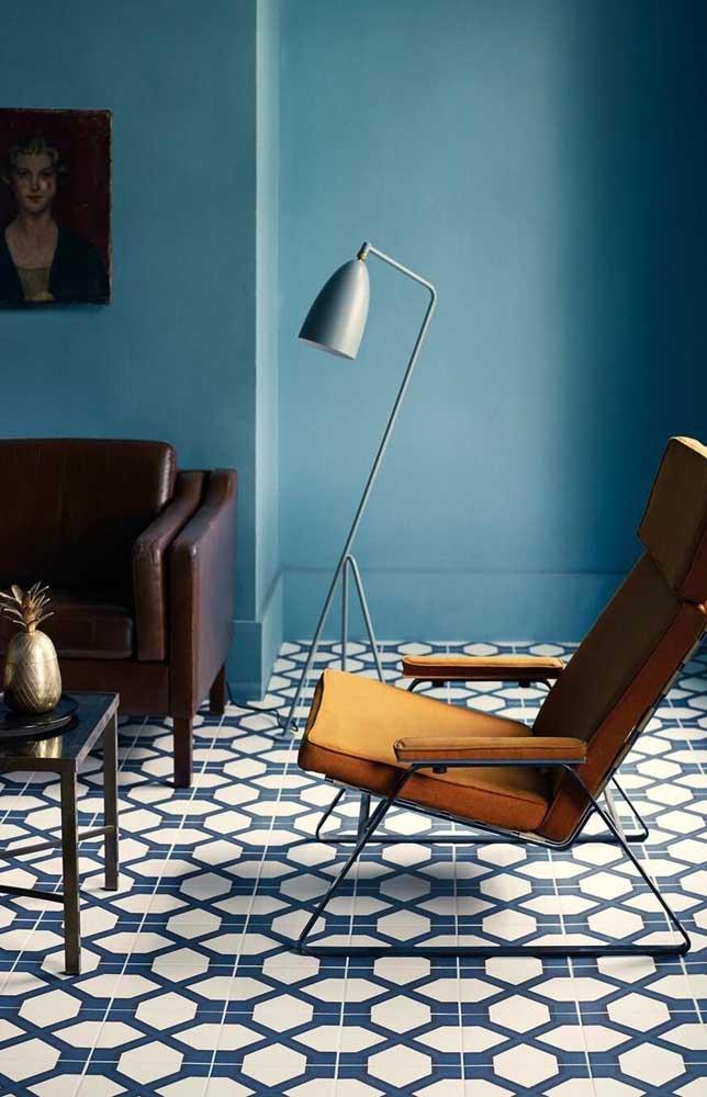 Nessa sala de estar, o azul é a cor predominante, mas ele cede espaço para o sofá marrom e a poltrona laranja