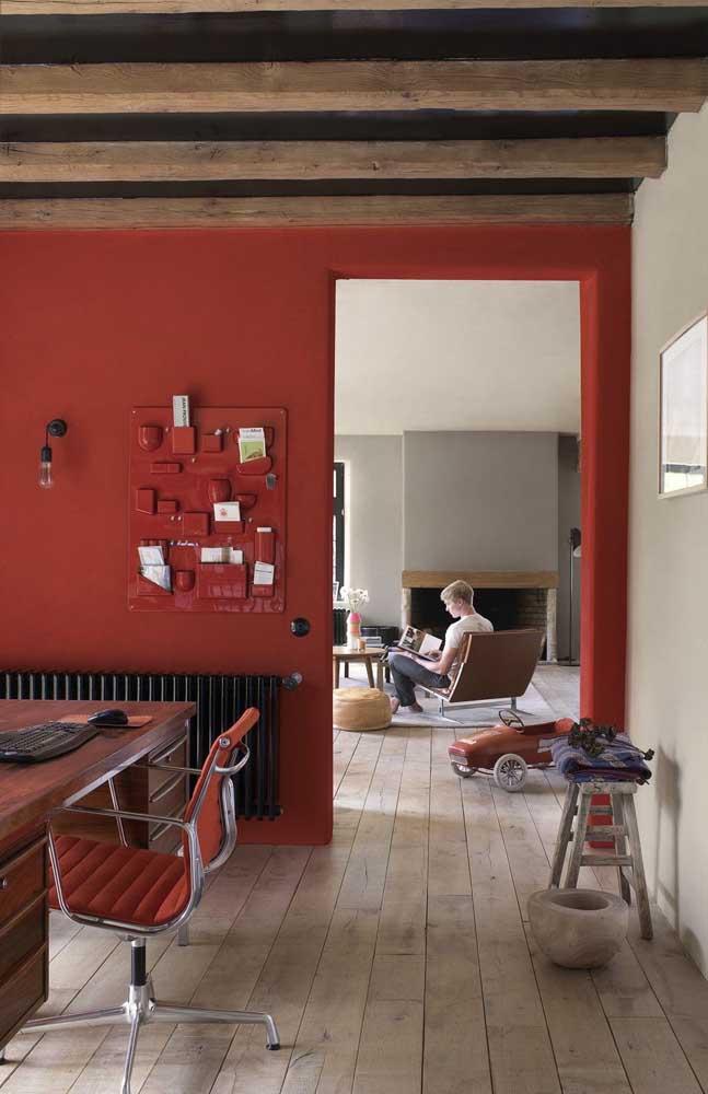 Parede pintada em um tom de vermelho profundo; a cor se harmoniza com as tonalidades naturais dos elementos em madeira