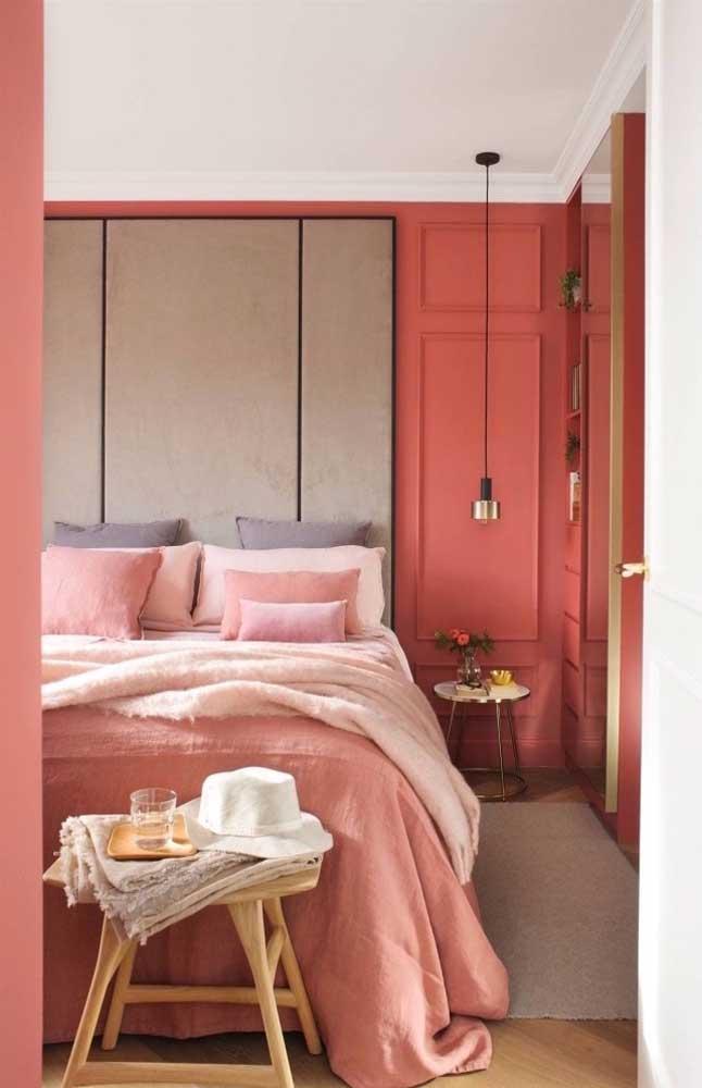 Estilosa, a parede com boiserie foi pintada de vermelho harmonizando-se com a roupa de cama em tons de rosa
