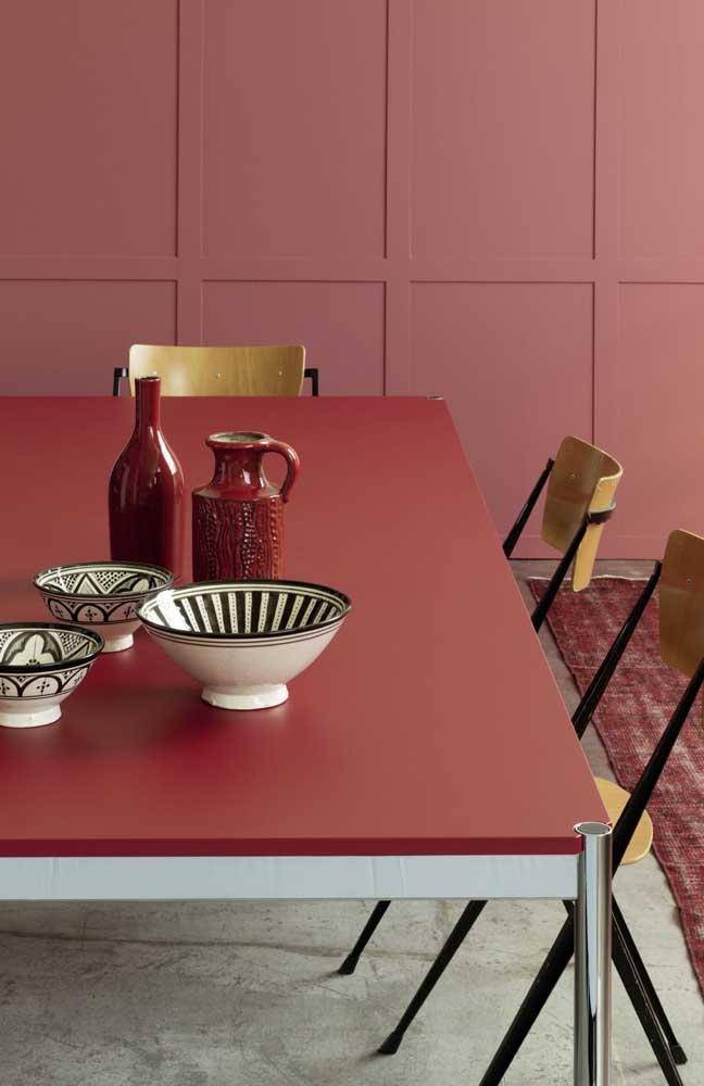Mesa de jantar com tampo vermelho; para contrastar, o chão de cimento queimado; destaque ainda para o tom rosa avermelhado da parede