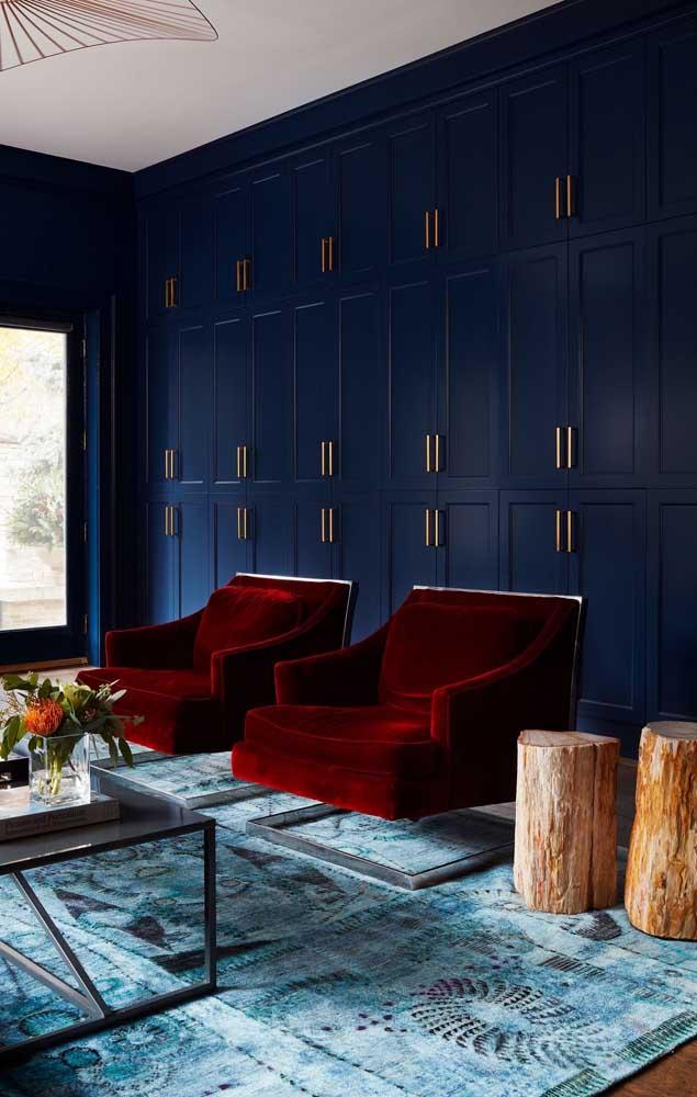 Quanto luxo cabe numa sala com sofá de veludo vermelho e parede azul petróleo? É de arrebatar os corações!