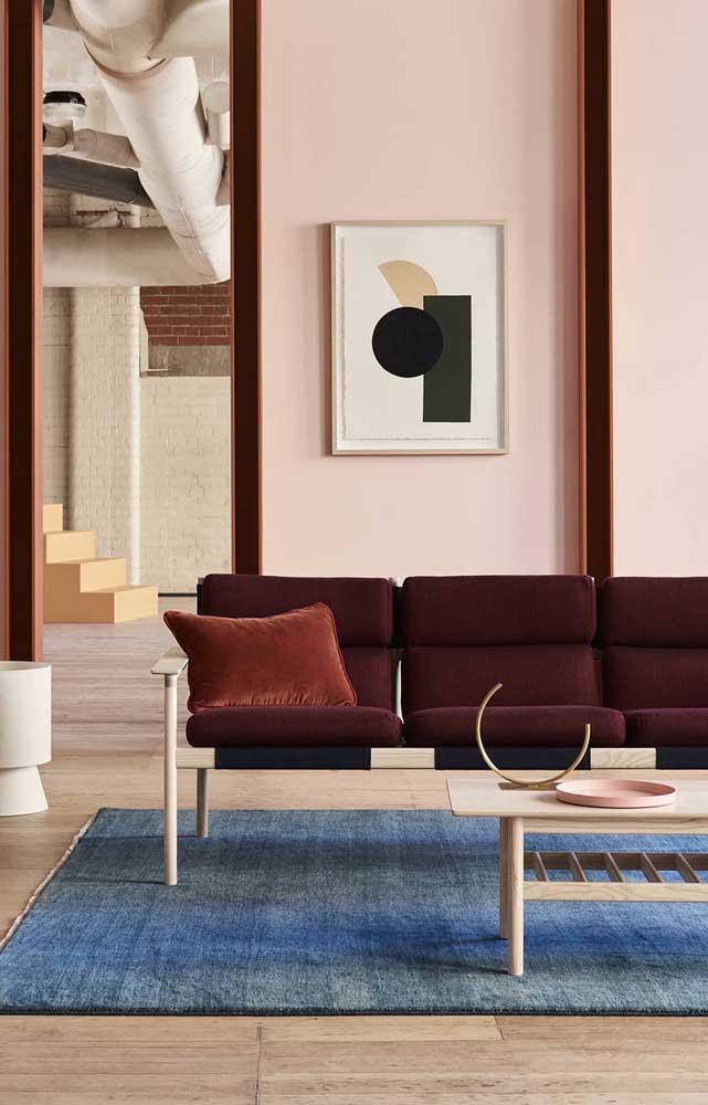 Um bom exemplo de como combinar o vermelho na decoração: a proposta aqui traz o vermelho profundo no sofá, o azul no tapete e o rosa na parede