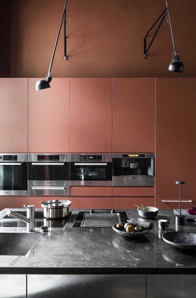 Nessa outra cozinha o vermelho aparece nos armários em um tom que puxa para o marrom