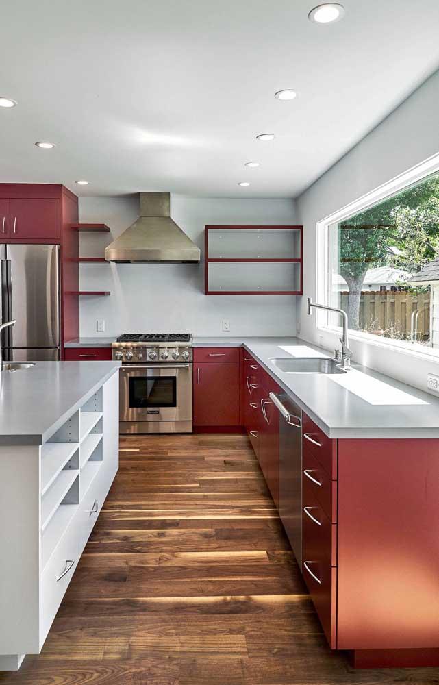 Cozinha de armários vermelhos; para combinar, piso de madeira natural e paredes brancas