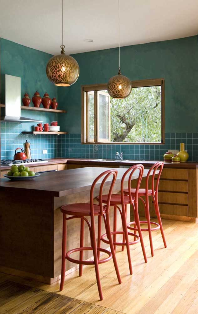 Essa cozinha em tom de azul ganhou banquetas vermelhas para criar contraste
