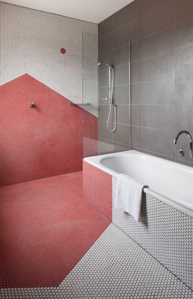 Nesse banheiro moderno, o vermelho entra nas pastilhas que ajudam a formar o desenho geométrico na parede e no chão