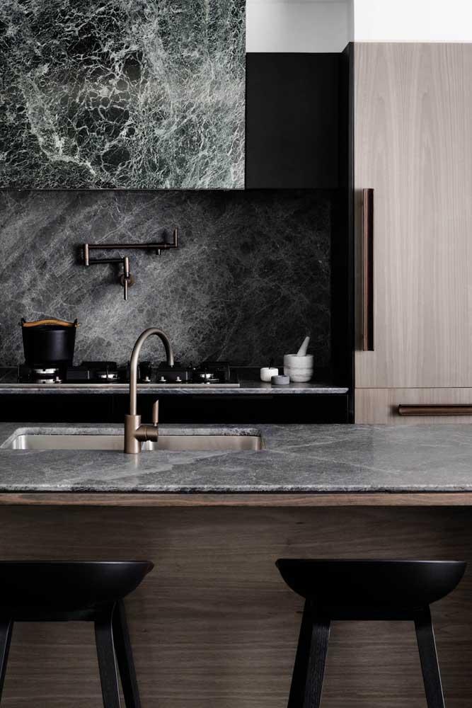 Ilha e bancada da cozinha com tampo de mármore e armários de madeira