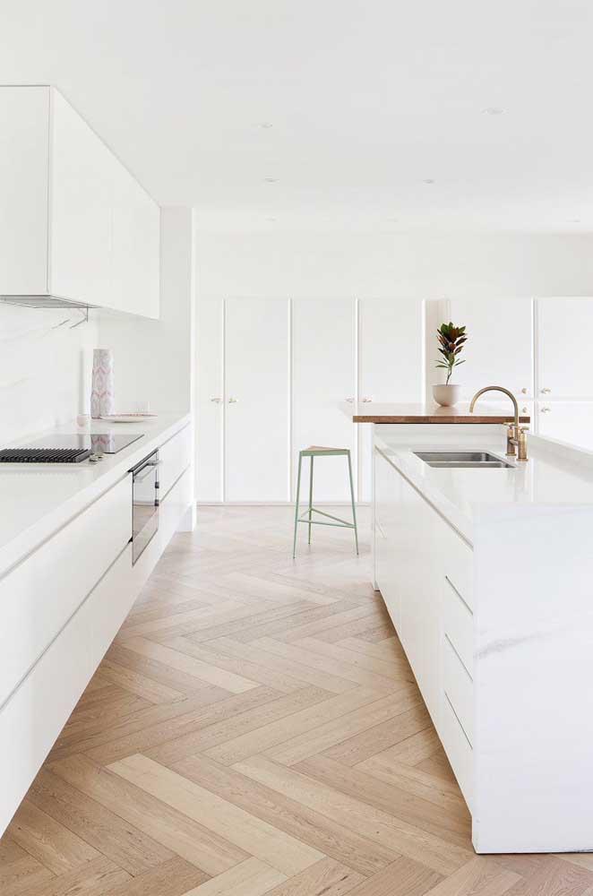 Cozinhas de estilo clean como essa da imagem combinam super bem com bancadas de pedra sintética