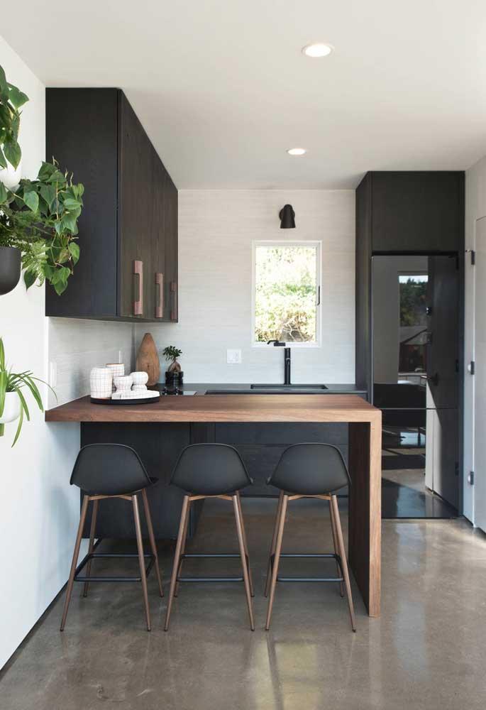 Balcão de madeira para a cozinha americana, mais aos fundos, a bancada da pia se destaca pela cor preta