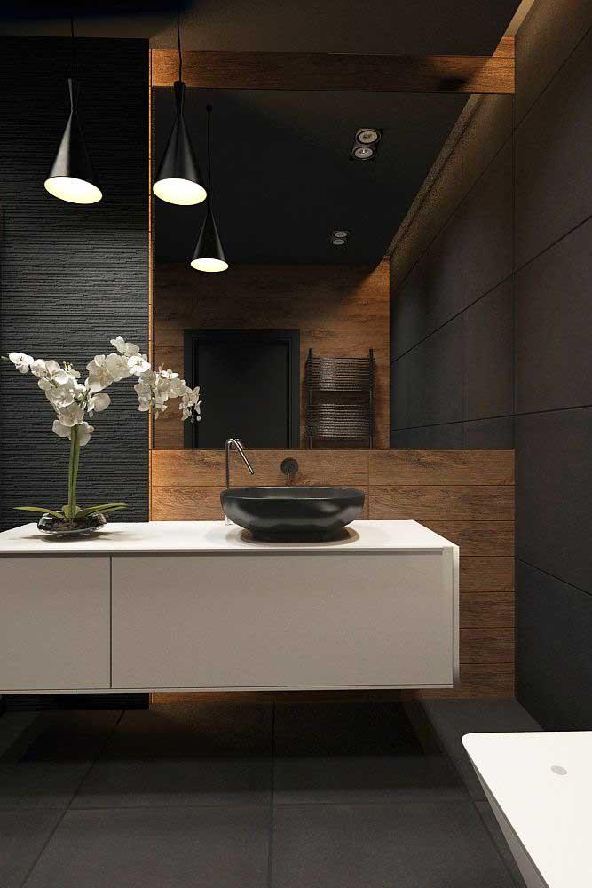 Essa proposta é para quem deseja causar impacto: banheiro decorado preto com detalhes em madeira; repare que a iluminação indireta é a grande responsável pelo efeito visual do projeto