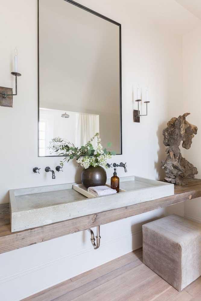 Banheiro decorado com estilo e elegância; destaque para a pia esculpida de granito sobre a bancada de madeira