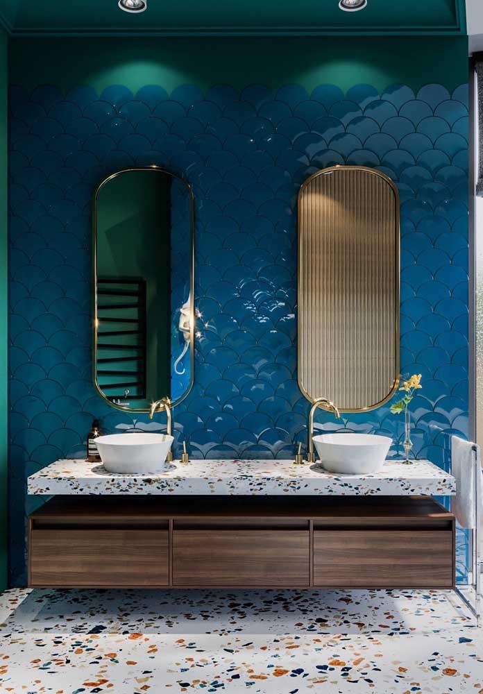 Que linda proposta por aqui: parede com revestimento escama de peixe azul e piso de granilite, os detalhes dourados fecham a decor