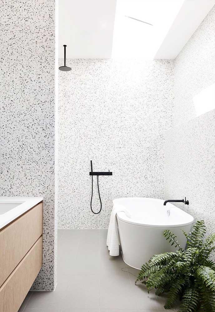 O charme desse banheiro pequeno e simples fica por conta da parede revestida com granilite, da iluminação natural e da pequena samambaia no canto