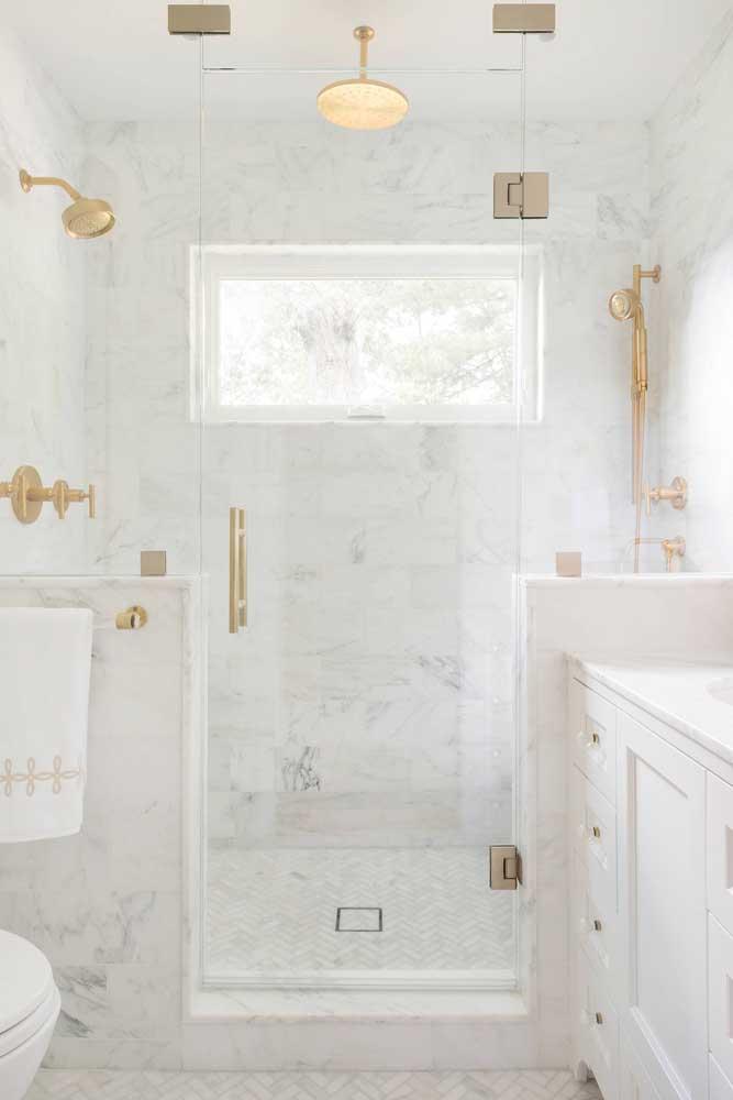 A brancura desse pequeno banheiro decorado foi quebrada pelos acessórios dourados