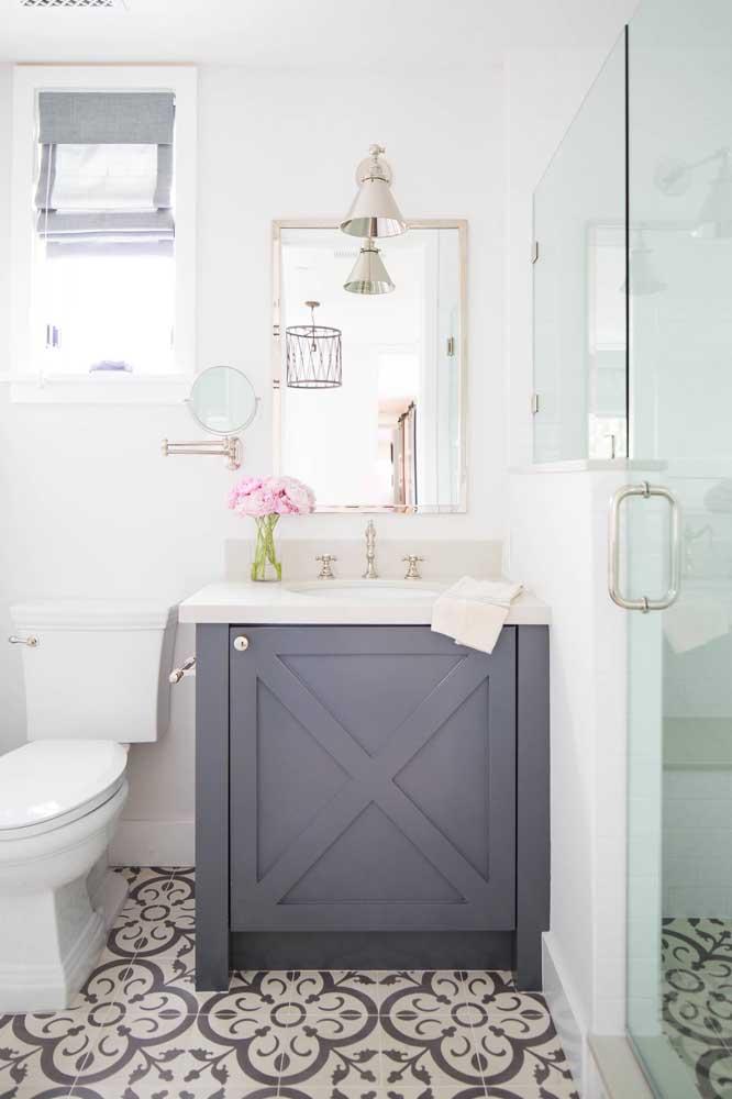Nesse pequeno banheiro decorado, vale a pena mencionar os detalhes que fazem toda a diferença, como o vasinho com flores na bancada ou a luminária sobre o espelho