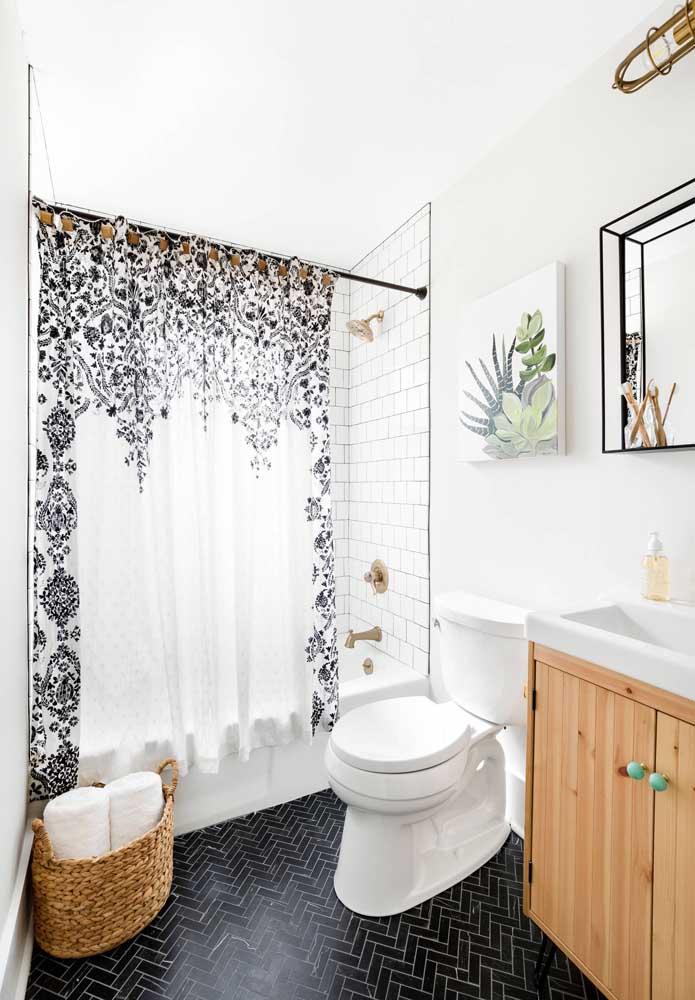 Um cesto de vime no chão, um quadro de suculentas na parede e uma cortininha charmosa integram a decoração desse banheiro simples