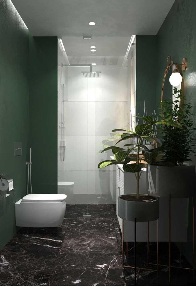 A parede verde traz profundidade ao banheiro decorado com plantas; o chão de mármore completa a proposta com elegância