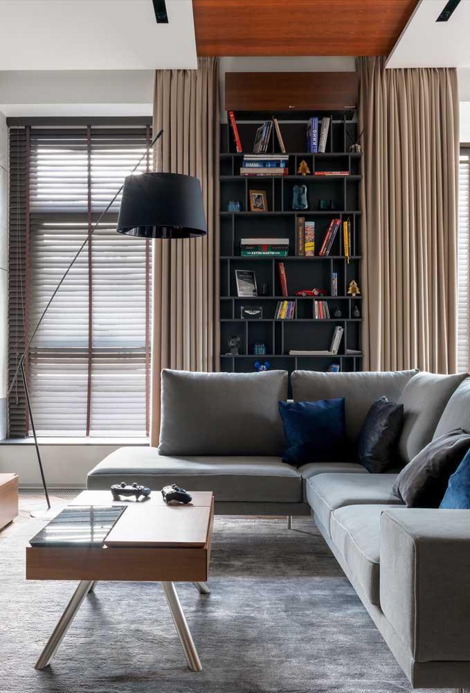 Nessa sala, as janelas contam com a presença de persianas para o controle da luz; a cortina é um bônus na decoração