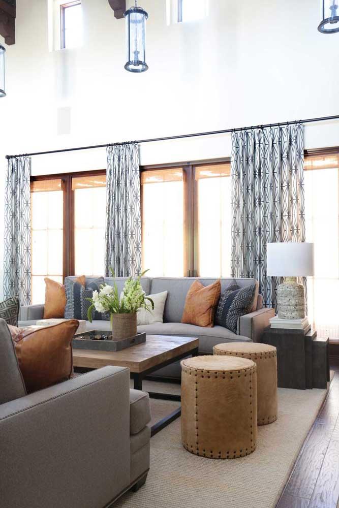 Nessa sala com pé direito duplo, a cortina se limita a altura da janela, mas repare que, em contrapartida, ela segue por todo o comprimento da parede