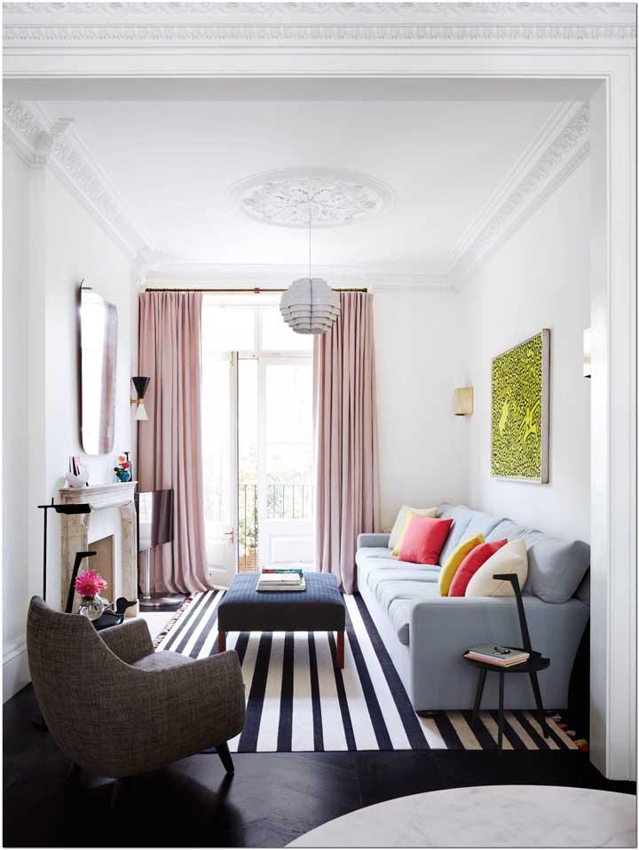 Essa sala que mescla o moderno com o clássico traz uma cortina longa de varão em um tom delicado de rosa