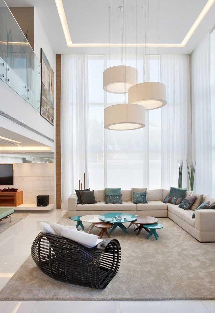 Longa, elegante, fluida: essa sala é puro conforto e sofisticação com a cortina branca que cobre toda a extensão do pé direito duplo