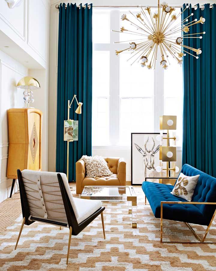 A proposta aqui foi valorizar o pé direito alto da sala com uma cortina de tom azul, semelhante a do sofá; os tons de amarelo completam a decor com um contraste delicado