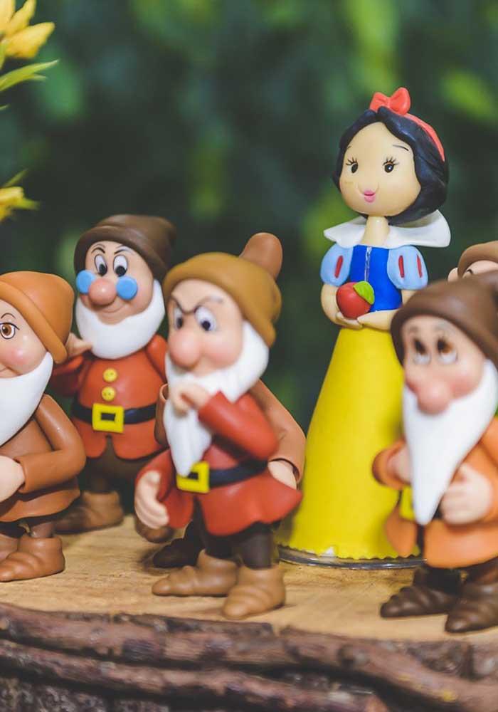 Os bonecos dos principais personagens do conto de fadas não podem faltar na decoração do centro de mesa Branca de Neve.