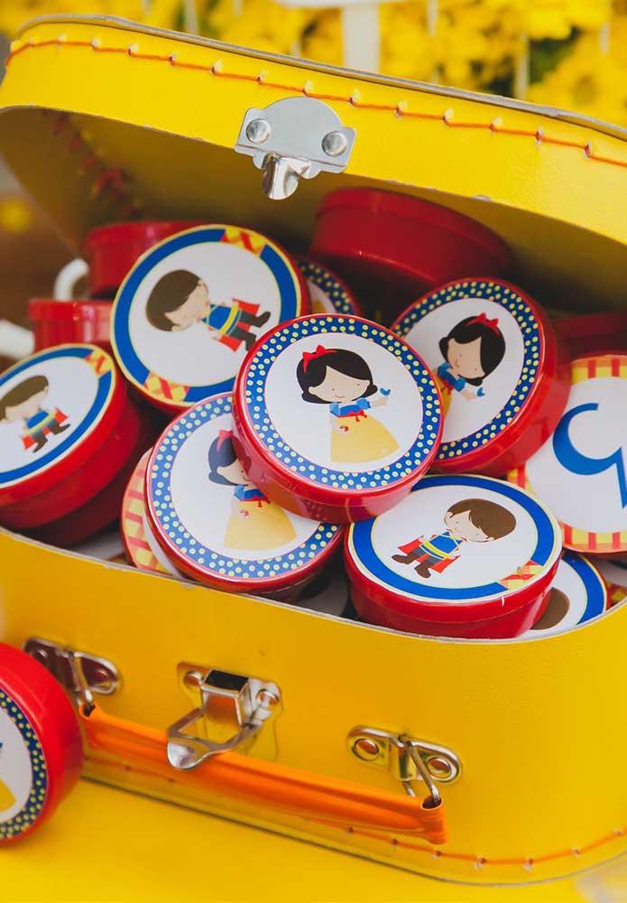 Latinhas personalizadas com os personagens da Branca de Neve. Coloque todas dentro de uma mala.