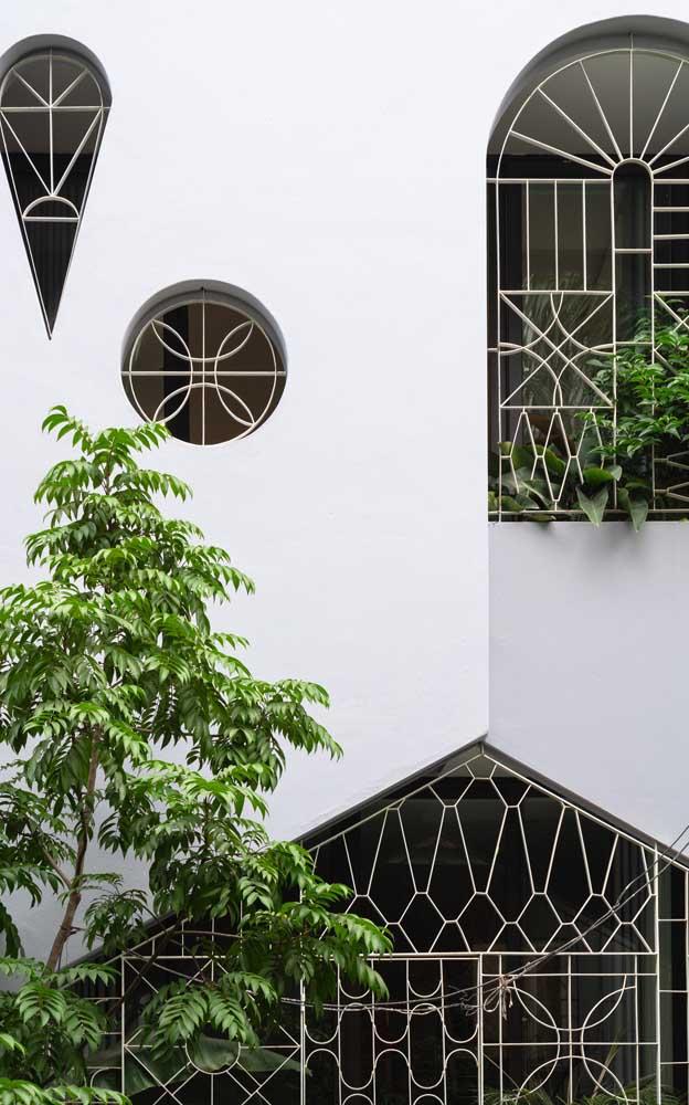 Grades de ferro com desenhos detalhados cobrindo as áreas vazadas da fachada da casa