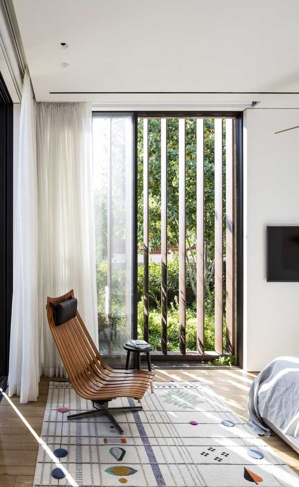 Essa sala de estar com vista para o jardim conta com um modelo de grade de madeira com espaçamento maior entre as barras