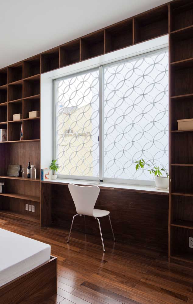 A janela que fica junto ao home office foi protegida por uma grade de ferro com desenhos de flores da vida