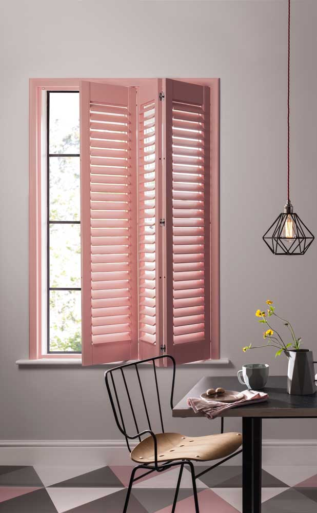 Esse ambiente romântico e despojado revela uma grade de ferro moderna e minimalista por trás da janela cor de rosa