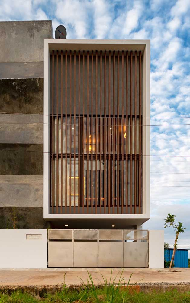 Aqui, as grades verticais de madeira são as responsáveis pela segurança e pela estética da fachada