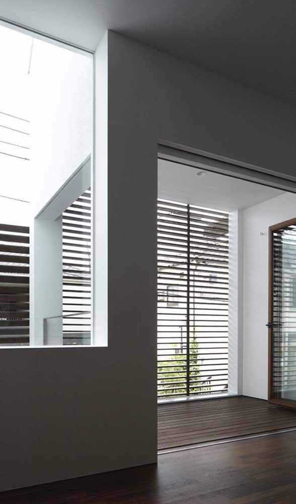 Grades de madeira atuando na fachada da casa como persianas, um belo efeito visual