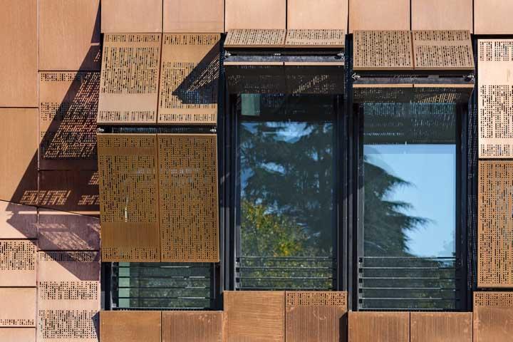 Um projeto e tanto por aqui: Placas metálicas perfuradas e coloridas formam as grades móveis dessa fachada