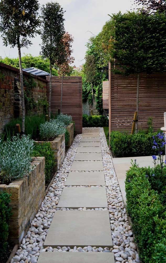 Aqui, as placas de granito sobrepostas as pedras seixos formam um lindo caminho em meio ao jardim