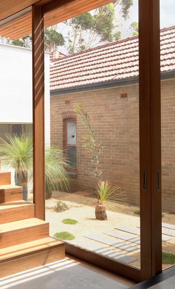 Já nessa área externa, as pedras de rio ajudam a valorizar a aparência rústica da fachada