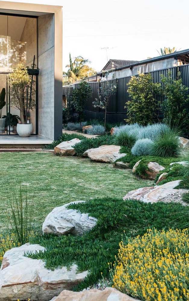 Pedras brutas naturais contornam esse amplo jardim na fachada