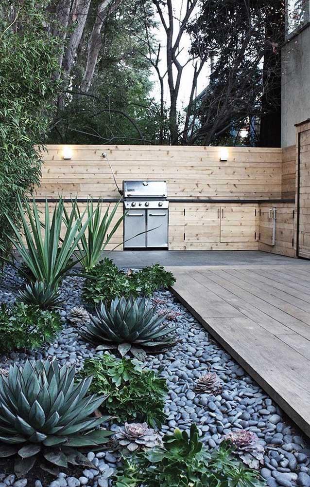 Em torno do deck de madeira, um jardim de pedras com cactos e suculentas