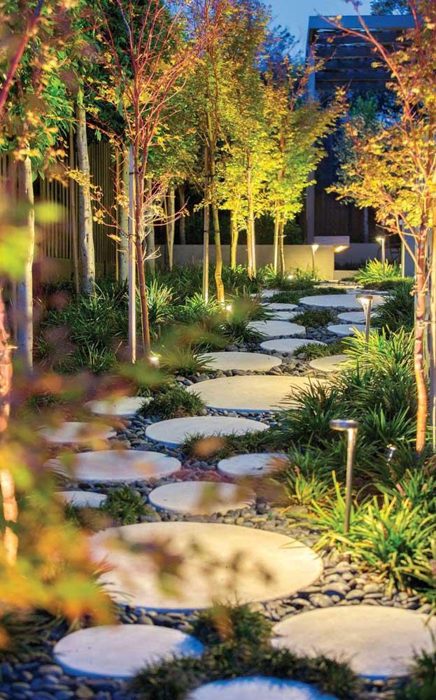 Sobre os seixos foram colocados placas redondas de pedras; o visual do jardim ficou ainda mais completo com a iluminação