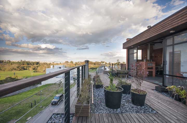 A varanda dessa casa traz madeira e pedras como opção de piso
