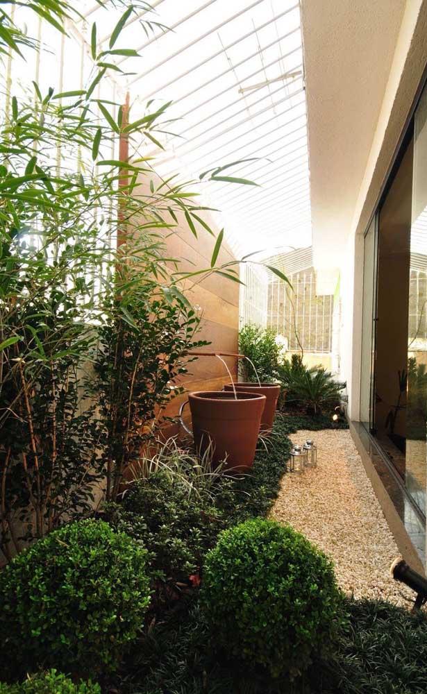 Esse jardim de inverno no corredor externo da casa traz um caminho de pedras seixos que contorna o desenho formado pelas plantas