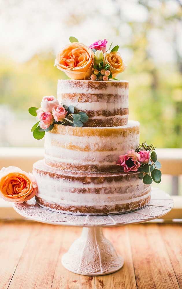 A festa de noivado simples pode contar com um bolo, como sugere o naked cake florido da imagem