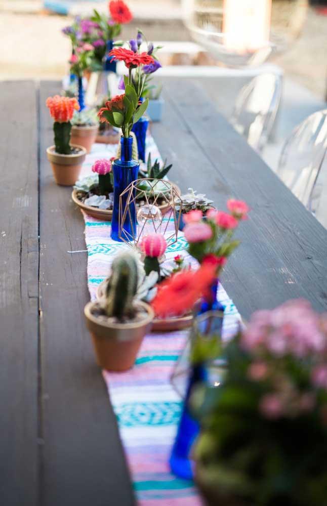 Flores e cactos decoram o centro da mesa da festa de noivado; opção para quem deseja algo rústico, colorido e alegre