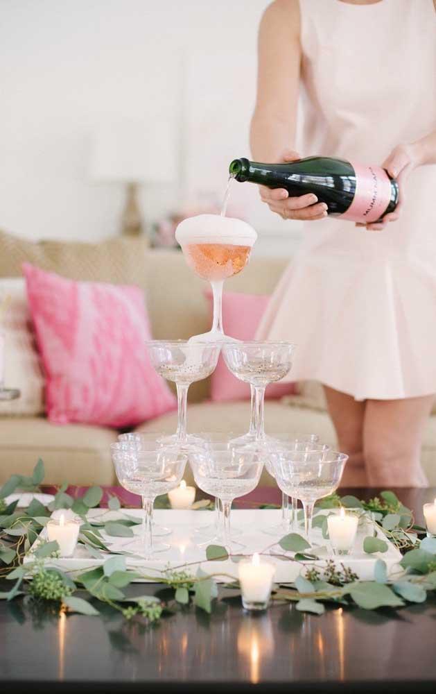 Uma ideia tradicional e que ainda faz muito sucesso em festas de noivado: pirâmide com as taças de champagne