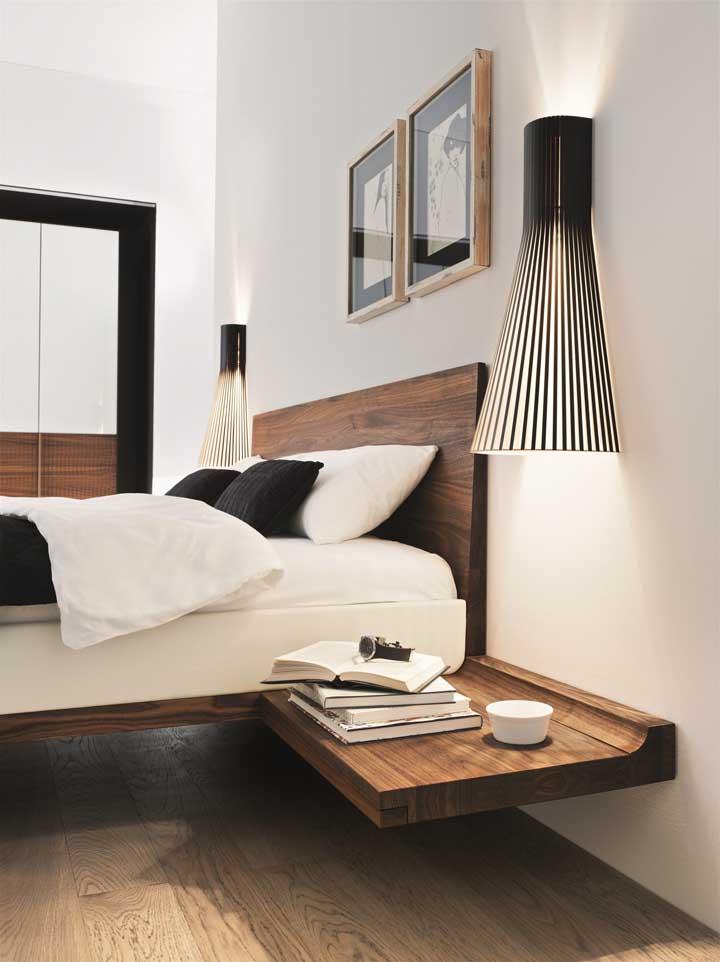 Prateleiras suspensas de madeira no lugar do criado mudo; visual clean e moderno para o quarto