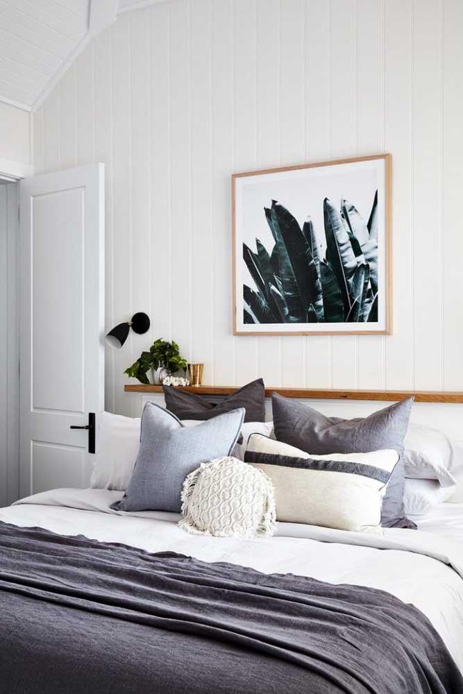 O quarto de casal branco e neutro traz uma prateleira estreita e comprida de madeira que atravessa todo o espaço acima da cabeceira