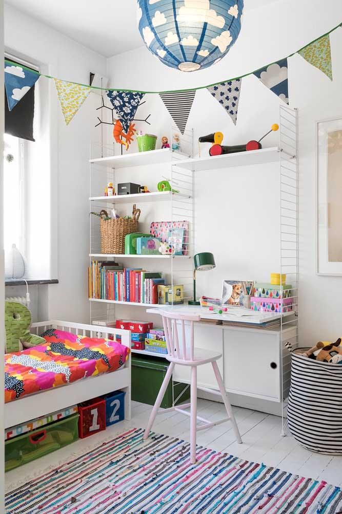 A estante com prateleiras no quarto infantil deixa à vista brinquedos e livros